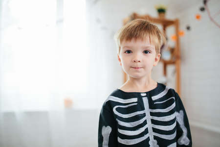 A child little boy in a skeleton costume is ready to celebrate Halloween. Boy in a halloween dress-up room.