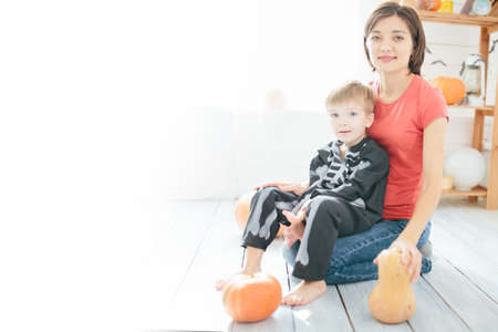 Happy family of mother and children prepare for Halloween in decorate the home