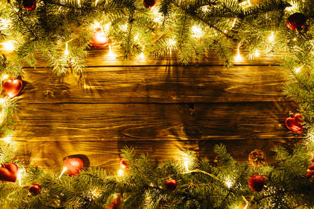 Border art design with Christmas tree, baubles and light garland Blurred Christmas background, with fir branches, fairy lights and christmas decorations on brown wooden plank