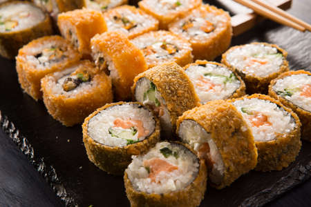 Set of baked sushi rolls with wasabi and ginger on black