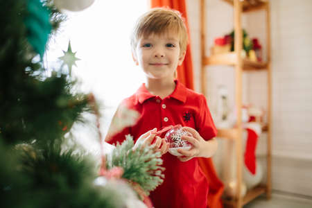 Cute little boy of about five year with a gift in a decorated Christmas room with a xmas tree