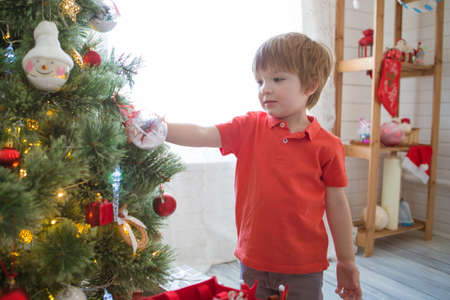 Little boy decorating the Christmas tree at home