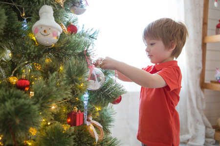 Little boy decorating the Christmas tree at home Archivio Fotografico