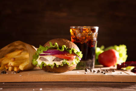Fresh big burger and glass cola on wooden table fast food concept