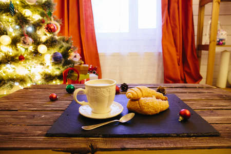 Mug with hot chocolate on a wooden table with Christmas decorations on a background of the Christmas tree. Drinks