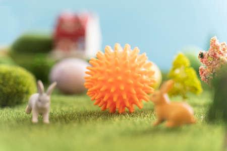 Ball coronavirus shape bunny toys and Easter eggs on a green grass. Fairy tale. covid-19 Reklamní fotografie