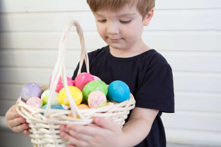 Boy with a basket with Easter eggs on a background of a white wall 版權商用圖片