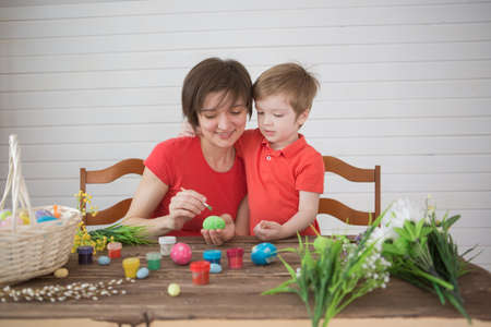 Mother and her son painting Easter eggs. Happy family preparing for Easter day 版權商用圖片