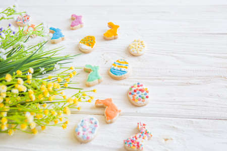 Easter cookies, bunnies and eggs with flowers on white wooden table