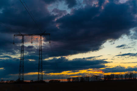 Electric high voltage pole at sunset background