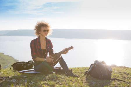 Woman with guitar ukulele in the mountains, amazing landscape, stunningly beautiful nature, mountains, sunset