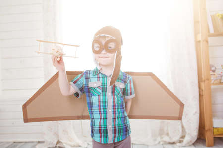 Children boy wearing pilot costume making ready to fly gesture standing on living room wooden floor at home Banco de Imagens