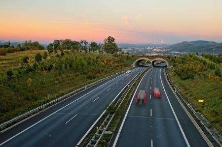일몰 ecoduct 아스팔트 고속도로, 거리에서 칼스 배드, 도로의 전망과 붉은 하늘 평행의 도시를 보름달 상승