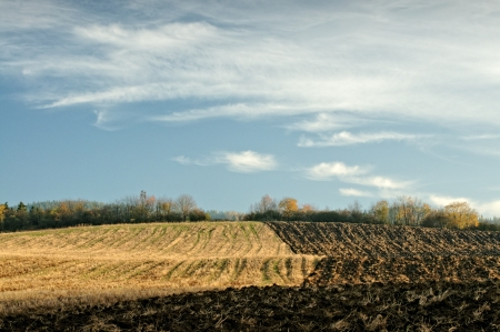afield: Autumn half-plowed field, blue sky with white clouds veil Stock Photo