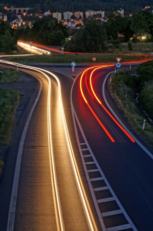 view to outside: The road in the evening with light stripes headlights, background in city, view from above