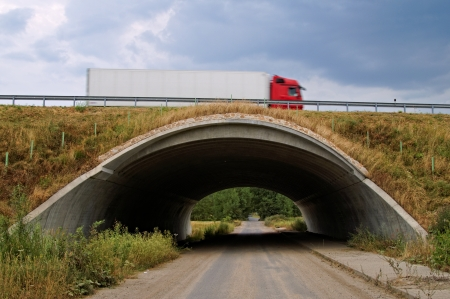 The road leading under the highway underpass, on a motorway underpass passes Truck photo