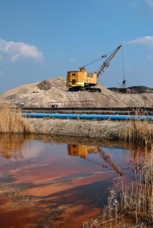 contaminacion del agua: Excavadora de la cuerda por relaves mineros entre los montones de arena, tanque de agua con lodo rojo, ribetes azules, la contaminación ambiental Foto de archivo