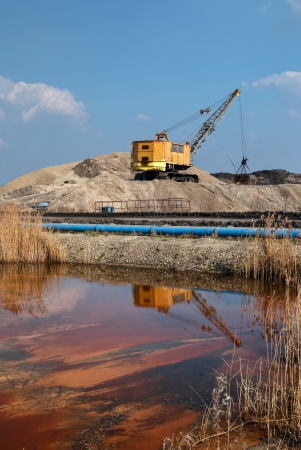 water contamination: Rope excavator for mining sludge among piles of sand, water tank with red sludge, blue piping, environmental pollution