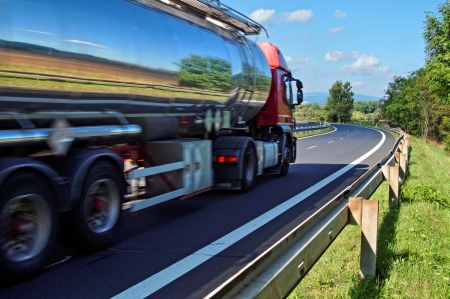 cisterne: Rispecchiando il paesaggio cromo camion cisterna in movimento su una strada, vista dal livello degli occhi Archivio Fotografico