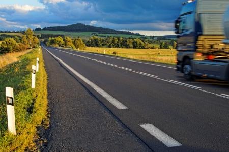 지평선을 향한 들판을 가로 지르는 아스팔트 도로, 도로상의 나가는 트럭, 지평선의 나무가 우거진 산, 어두운 폭풍우 구름