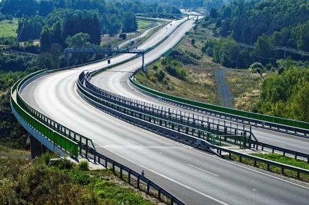 Lege snelweg tussen de bossen in het landschap, in het midden van de snelweg elektronische tolheffing poort, in de verte op de snelweg motorfiets, auto en bruggen