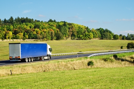 Autumn landscape with road and truck, in the foreground meadow, forest in the background Standard-Bild
