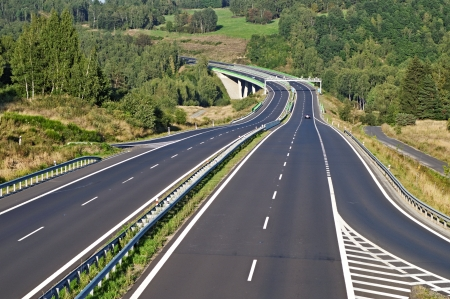 Empty highway between forests in the landscape, in the middle of the highway electronic toll gate and bridge, in the distance on the highway car, view from above Standard-Bild