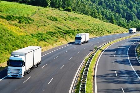 高速道路上から緑豊かな風景、草原、森林、斜面で 3 対向白いトラックの眺め
