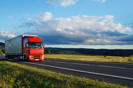 Landelijk landschap met weg-en bewegende rode vrachtwagen, Cerulean hemel met wolken