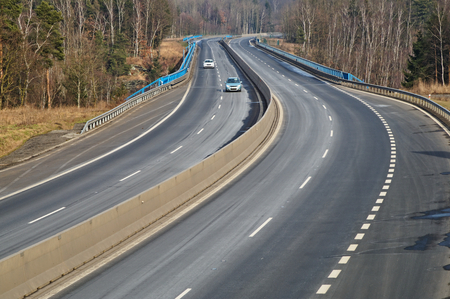 guardrail: Highway in the forest, two moving cars, bare trees, view from above