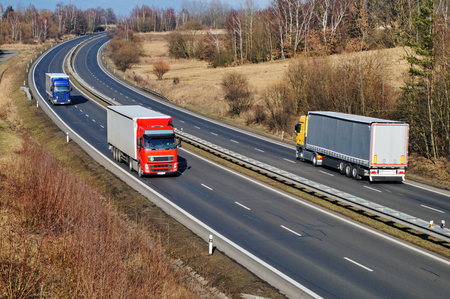 Landscape with highway, the highway ride three trucks, early spring, view from above Standard-Bild