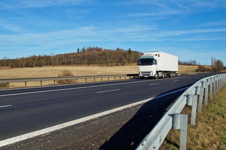 흰색 트럭을 운전하는 충돌 장벽이 늘어선 도로와 봄 풍경