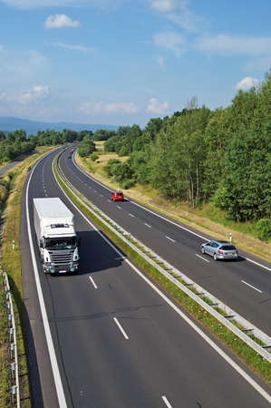 Highway passing through the countryside, going down the highway truck and passenger cars, view from above
