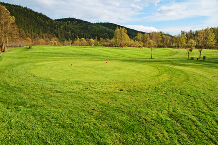 Red teeing ground on the golf course, red tee marker, wooded mountains in the background photo