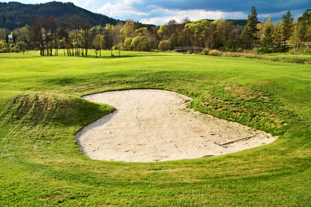 White sand bunker on the golf course, wooded mountains in the background photo