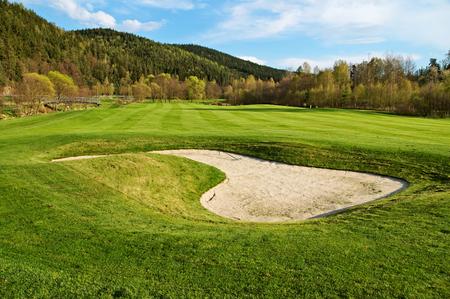 Weiße Sandbunker auf dem Golfplatz, bewaldeten Bergen im Hintergrund