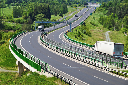 toll: The highway between woods, in the middle of the highway electronic toll gates, three moving trucks, in the distance Bridges
