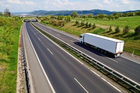 야생 동물을위한 전환과 함께 복도 고속도로, 고속도로는 도시와 숲이 우거진 산들을 배경으로 하얀 트럭을 간다.