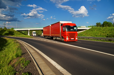 Red truck driving along the highway through the countryside, in the background the bridge, under which runs a white truck, white clouds in the blue sky