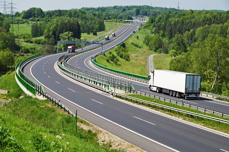 The highway between woods, in the middle of the highway electronic toll gates, moving trucks, in the distance Bridges photo
