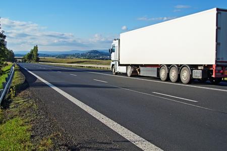 道路、道路と風景の距離での白いトラックを行くは、山と村 写真素材