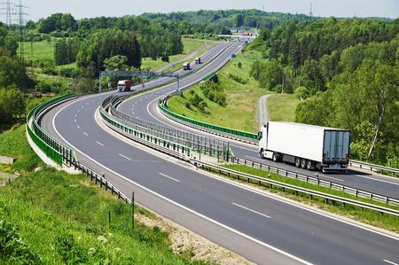 De snelweg tussen de bossen, in het midden van de snelweg elektronische tolpoorten, bewegende trucks, in de verte Bruggen