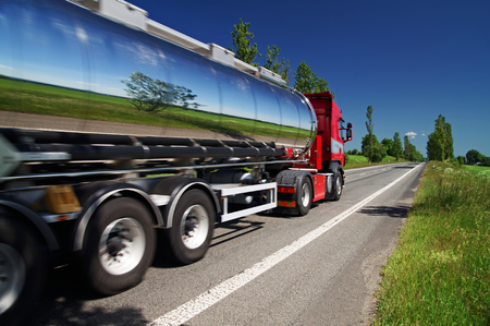 Mirroring the landscape chrome tank truck moving on a highway, view from eye level