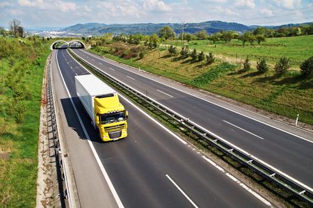 야생 동물을위한 전환과 복도 고속도로, 고속도로 백그라운드에서 도시와 숲이 우거진 산에서 노란색 트럭 간다, 위에서 볼 스톡 콘텐츠