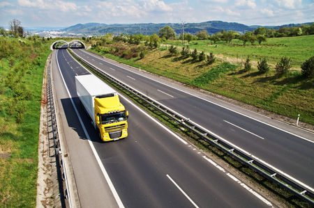 Corridor highway with the transition for wildlife, the highway goes yellow truck, in the background the city and forested mountains, view from above
