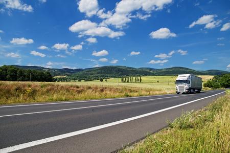 도로는 푸른 하늘에 녹색 옥수수 밭의 배경과 나무가 우거진 산, 흰 구름, 흰색 트럭을 운전하는 농촌 풍경