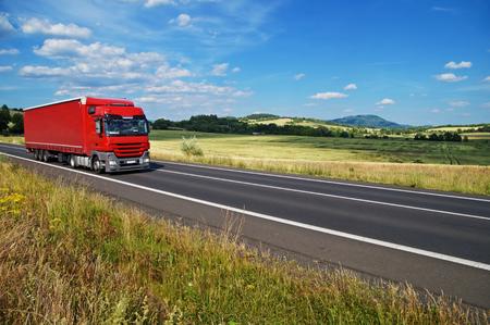 녹색 옥수수 밭과 숲이 우거진 산, 푸른 하늘에 흰 구름의 배경에서 빨간색 트럭 운전하는도 [NULL]와 농촌 풍경