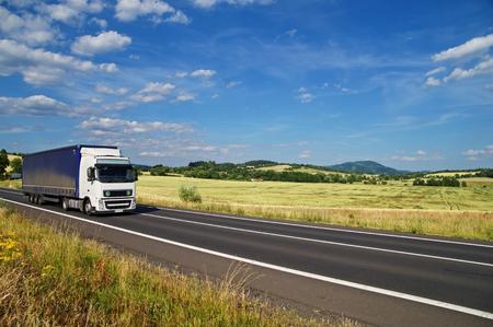 あなたは道路景観緑トウモロコシ畑と緑豊かな山々 を背景に白い青空に雲の白いトラックを運転、