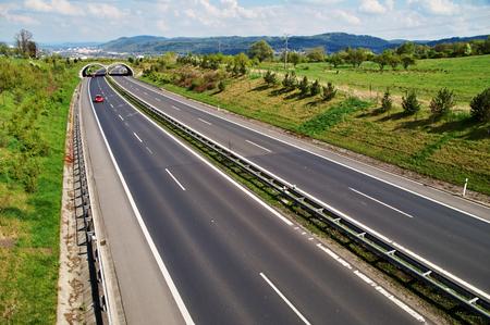 背景の都市で、距離 3 つの赤い車に、動物のための移行と廊下を高速道路や森林に覆われた山を上から表示します。