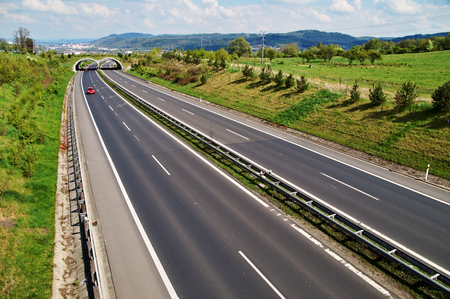 Corridor highway with the transition for animals, in the distance three red car, in the background the city and forested mountains, view from above
